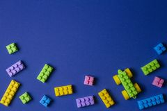 Colorful plastic toy car building blocks on blue background.  royalty free stock images