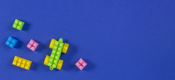 Colorful plastic toy car building blocks on blue background.  royalty free stock photography