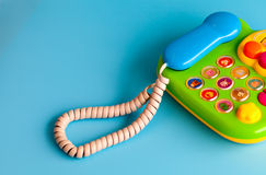 Colorful plastic toy mobile phone on a blue background for children. Royalty Free Stock Photo