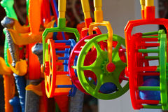 Colorful plastic toys. A collection of colorful plastic toys outside at a market stall - plastic swords in the background Royalty Free Stock Photos
