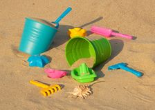 Colorful plastic toys on the sandy beach Stock Photos