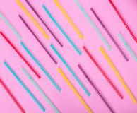 Colorful plastic tube with white polka dots for drinks. Scattered on a pink background stock image