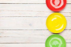 Colorful plates over white wooden table background Royalty Free Stock Images