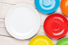 Colorful plates over white wooden table background Royalty Free Stock Photography