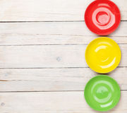 Colorful plates over white wooden table background Stock Photos
