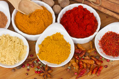 Colorful plates of spices on wooden table Royalty Free Stock Photo