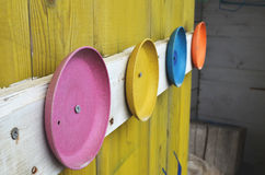 Colorful plates on wooden wall. Colorful plates on yellow wooden wall Royalty Free Stock Image