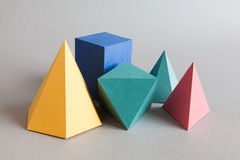 Colorful platonic solids, abstract geometric figures on gray background. Pyramid prism rectangular cube yellow blue pink. Green colored shapes. Shallow depth of Stock Image