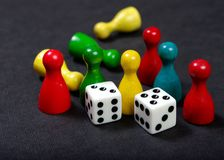 Colorful play figures with dice on board. royalty free stock image