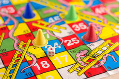 Colorful play figures and dice on board.jpg Royalty Free Stock Photo