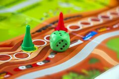 Colorful play figures and plastic chips with dice on сolored board. Board games for children and adults. Family and friendly