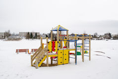 Colorful playground frozen snowy lake house winter Stock Images