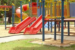 Colorful playground in public park, slide and swing on yard activities for children.  royalty free stock image