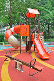 Colorful playground structure with plenty of Games for kids. The games include slides, climbers, playhouse, seesaw and swing Stock Images