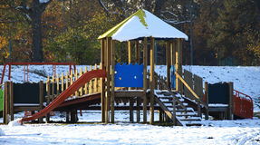 Colorful playground after winter snow. Empty wooden colorful playground covered with snow Royalty Free Stock Images
