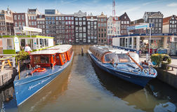 Colorful Pleasure boats stand moored on Damrak Canal Royalty Free Stock Images