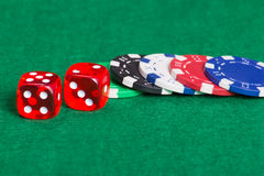 Colorful poker chips and dice on a green felt Stock Image
