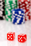 Colorful poker chips and dices. A pair of dices and stacks of colorful poker chips Stock Photo