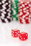 Colorful poker chips and dices. A pair of dices and stacks of colorful poker chips Stock Photos