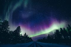 Colorful polar arctic Northern lights Aurora Borealis activity in winter Finland royalty free stock images