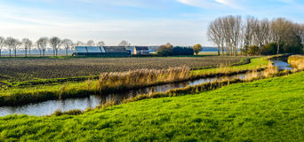 Colorful polder landscape with meandering stream Stock Photos