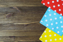 Colorful polka dot napkins on wooden background. Royalty Free Stock Images