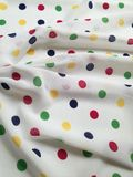 Colorful polka dots background. Background of white fabric texture with colorful polka dots stock photo