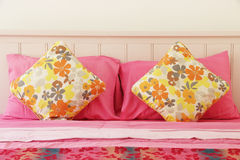 Colorful polka pillow on pink bed Royalty Free Stock Photos