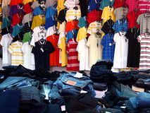 Colorful polo shirts and piles of denim jeans on display at a clothes store Stock Photo