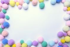 Colorful pom poms on white copy space background royalty free stock image