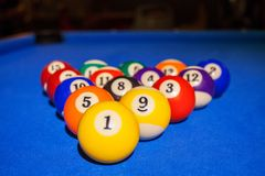 Colorful pool balls on billiard table. Colorful billiard balls in triangle arranged on a blue pool table Stock Image