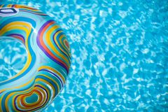 Colorful pool float in blue swimming basin Stock Photos