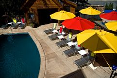 Colorful Pool Umbrellas. Lounge chairs and colorful umbrellas beside a pool and patio Royalty Free Stock Photography