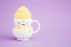 Colorful Porcelain Mug as Snowman on purple background, Stock Photo