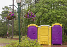 Colorful Portable Outdoor Toilet with Flowers. Bright portable toilets in a setting with hanging flower baskets Stock Image