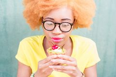 Colorful portrait of an african woman with sweet dessert. Portrait of a pretty african woman in yellow t-shirt holding a sweet dessert with cherry on the green Royalty Free Stock Photo