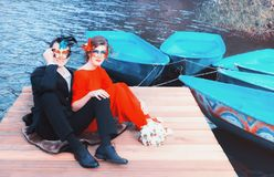 Happy Couple In Masquerade Masks. Colorful portrait of happy couple in masquerade masks - elegantly dressed men and women sitting on the pier by the lake with royalty free stock photography