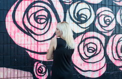 Colorful portrait of pretty young blond woman posing on graffiti wall background in black dress Stock Photography