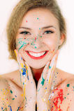 Colorful portrait of smiling woman in paint with red lips Royalty Free Stock Photo