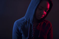 Colorful portrait of thoughtful woman with dark skin wearing hoodie. Colorful photo of a pensive and cool woman with dark skin wearing hoodie. Red and blue color royalty free stock photos