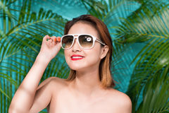 Colorful portrait of young attractive asian woman in sexy dress. And wearing sunglasses over blue background. Summer beauty concept Royalty Free Stock Image