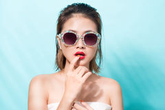 Colorful portrait of young attractive asian woman in sexy dress. And wearing sunglasses over blue background. Summer beauty concept Royalty Free Stock Photos