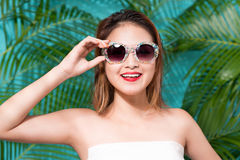 Colorful portrait of young attractive asian woman in sexy dress. And wearing sunglasses over blue background. Summer beauty concept Stock Images