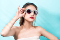 Colorful portrait of young attractive asian woman in sexy dress. And wearing sunglasses over blue background. Summer beauty concept Stock Photo