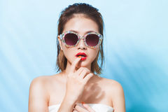 Colorful portrait of young attractive asian woman in sexy dress. And wearing sunglasses over blue background. Summer beauty concept Royalty Free Stock Images