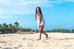 Colorful portrait of young attractive asian woman in white dress on the tropical beach of Bali island, Indonesia. Royalty Free Stock Photo