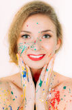 Colorful portrait of young smiling woman in paint with red lips Royalty Free Stock Image