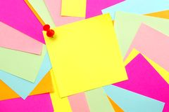 Colorful Post it Note Background. Blank yellow post it note with thumb tack and colorful scattered note background Stock Image