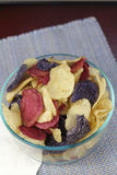 Colorful Potato Chips in a Clear Bowl. Red Crimson, Purple Majesty, Chipeta and Atlantic potato chips food. Close-up of red crimson, purple blue and yellow white stock image