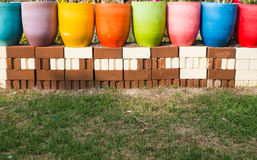 Colorful pots on the grass. Many colorful pots on the grass in the garden Royalty Free Stock Images